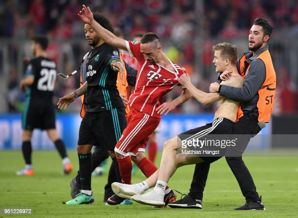A pitch invador grabs the shirt of Franck Ribery of Bayern Muenchen following the UEFA Champions League Semi Final First Leg match between Bayern...