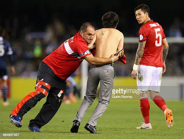 A pitch invador is tackled by security during the AFC Asian Champions League match between the Melbourne Victory and Guangzhou Evergrande at Etihad...