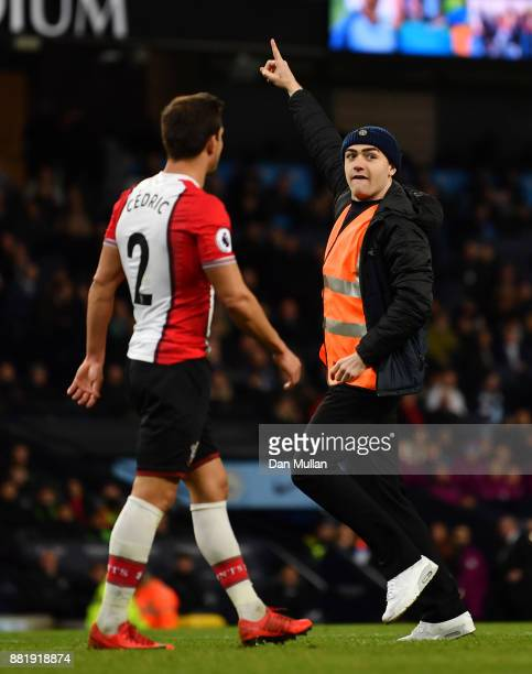 A pitch invador runs onto the pitch as Cedric Soares of Southampton looks on during the Premier League match between Manchester City and Southampton...