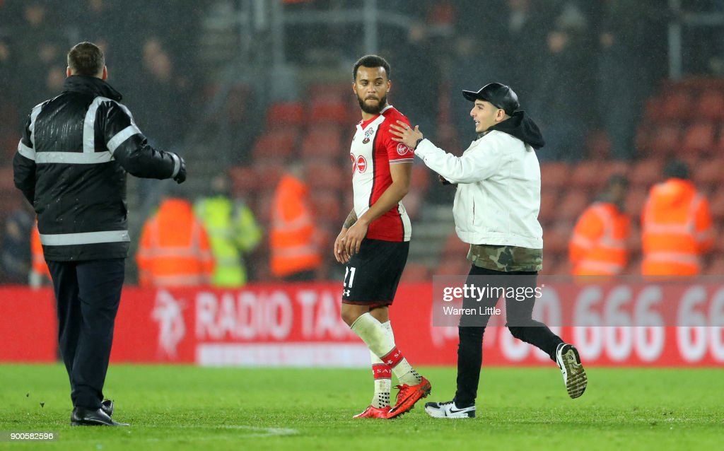 A pitch invador runs to Ryan Bertrand of Southampton after the Premier League match between Southampton and Crystal Palace at St Mary's Stadium on January 2, 2018 in Southampton, England.
