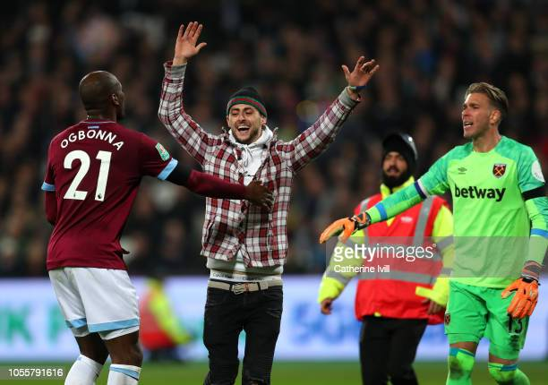 A pitch invador speaks to Angelo Ogbonna of West Ham United during the Carabao Cup Fourth Round match between West Ham United and Tottenham Hotspur...