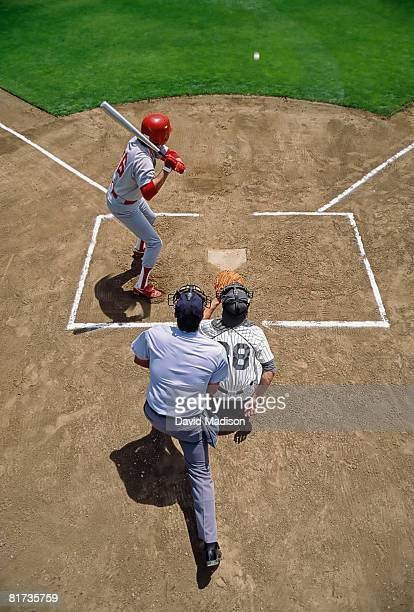 pitched ball coming towards baseball batter with catcher and umpire in foreground. - バッティング ストックフォトと画像