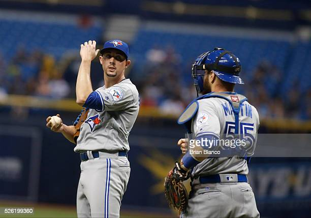 Pitcher Aaron Sanchez of the Toronto Blue Jays speaks with catcher Russell Martin on the mound after walking Brad Miller of the Tampa Bay Rays during...
