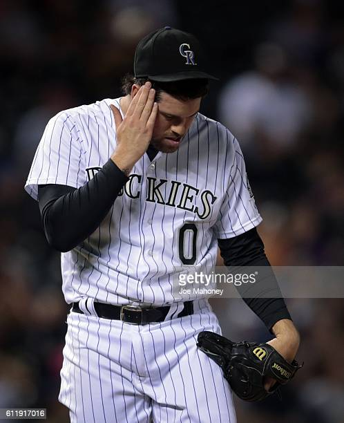 Pitcher Adam Ottavino of the Colorado Rockies wipes his head after Chris Carter of the Milwaukee Brewers hit the gamewinning home run in the 10th...