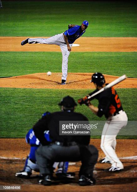 Pitcher Alexi Ogando of the Texas Rangers throws a pitch against the San Francisco Giants in the first meeting between the two teams since the World...