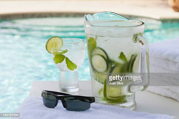 Pitcher and glass of water with cucumber by pool