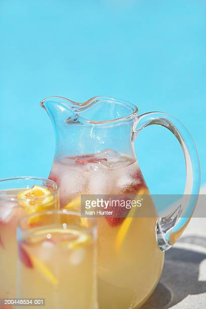 Pitcher and glasses of strawberry lemonade beside swimming pool