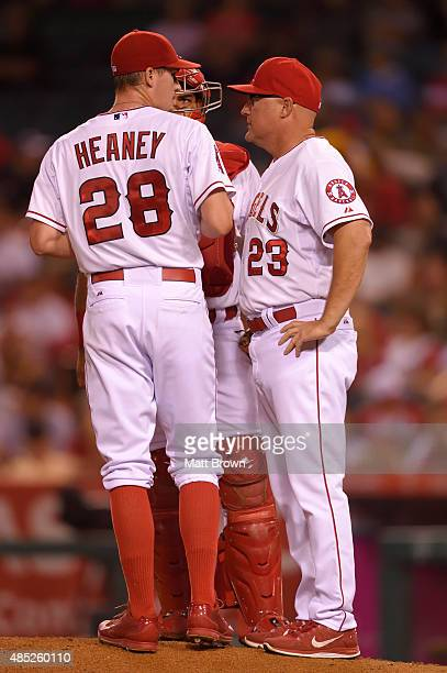 Pitcher Andrew Heaney catcher Carlos Perez and pitching coach Mike Butcher of the Los Angeles Angels of Anaheim talk on the mound during the game...
