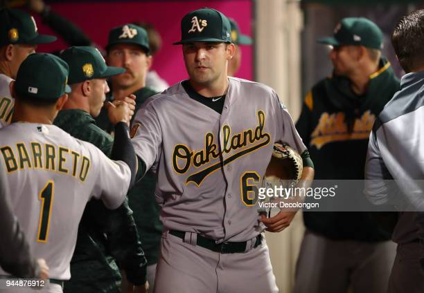 Pitcher Andrew Triggs of the Oakland Athletics is congratulated with teammates after leaving the game in the sixth inning during the MLB game against...