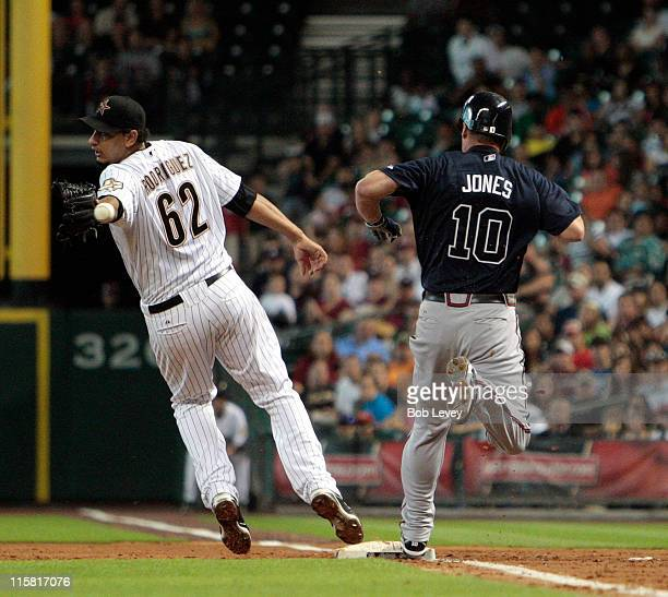 Pitcher Aneury Rodriguez of the Houston Astros can't handle the throw as Chipper Jones of the Atlanta Braves beats it to the bag at Minute Maid Park...