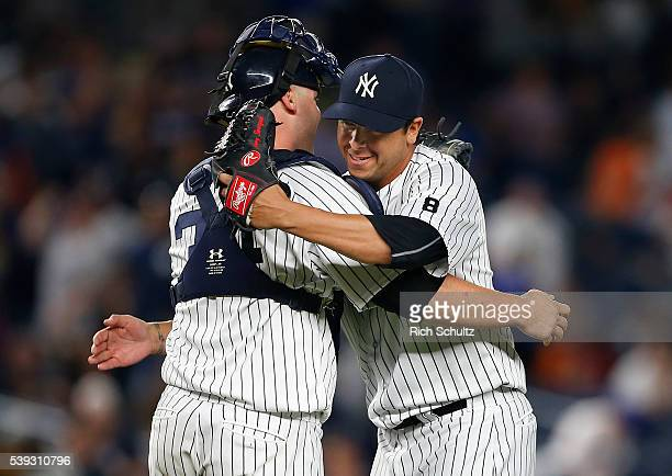 Pitcher Anthony Swarzak of the New York Yankees hugs catcher Brian McCann after getting the final out in the ninth inning against the Detroit Tigers...