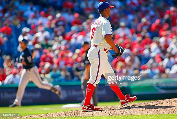 Pitcher Antonio Bastardo of the Philadelphia Phillies looks out to center field as Ryan Braun of the Milwaukee Brewers rounds third base after...