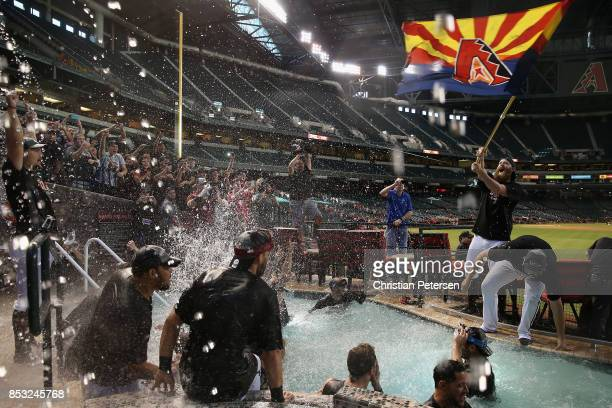 Pitcher Archie Bradley of the Arizona Diamondbacks waves an Arizona flag as the team celebrates in the outfield pool after defeating the Miami...