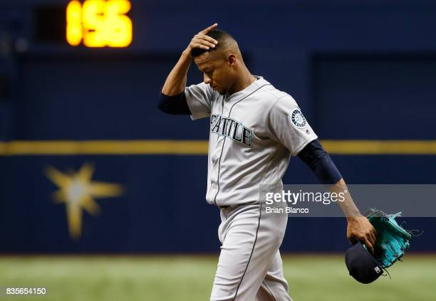 Pitcher Ariel Miranda of the Seattle Mariners makes his way to the dugout after being taken off the mound by manager Scott Servais after allowing a...