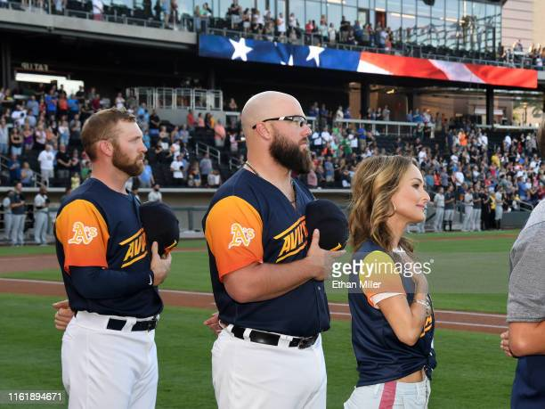 Pitcher Ben Bracewell and catcher Cameron Rupp of the Las Vegas Aviators and chef Giada De Laurentiis stand on the field as the American national...