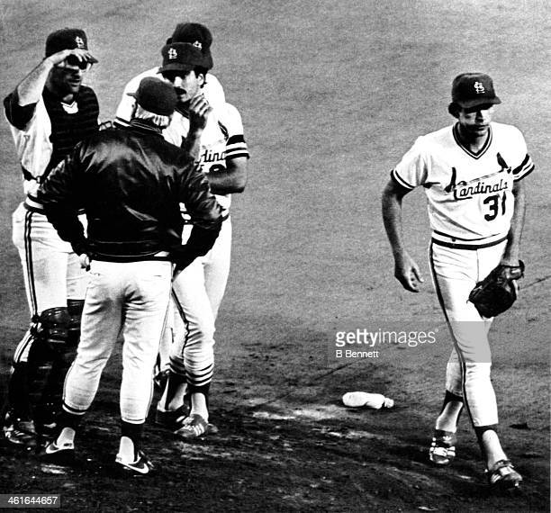 Pitcher Bob Forsch of the St Louis Cardinals walks away from the mound after being pulled in the 6th inning as manager Whitey Herzog talks to catcher...