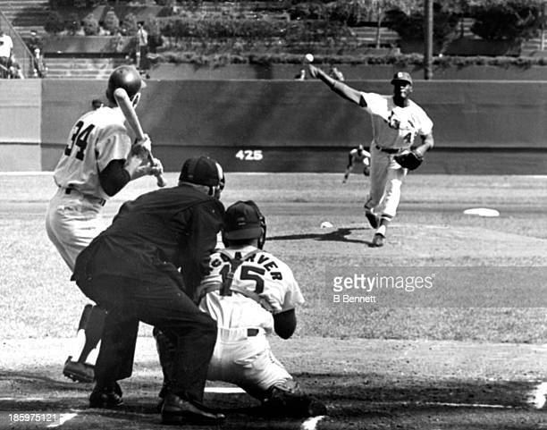 Pitcher Bob Gibson of the St Louis Cardinals throws the first pitch to Phil Linz of the New York Yankees as catcher Tim McCarver and umpire Frank...