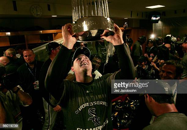 Pitcher Bobby Jenks of the Chicago White Sox celebrates in the locker room with the championship trophy after winning Game Four of the 2005 Major...