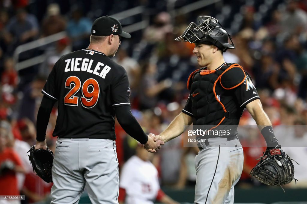 Pitcher Brad Ziegler #29 and catcher J.T. Realmuto #11 of the Miami Marlins celebrate the Marlins 7-3 win over the Washington Nationals at Nationals Park on August 8, 2017 in Washington, DC.