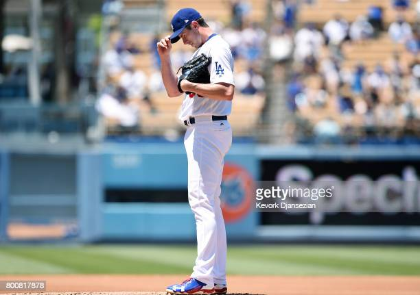 Pitcher Brandon McCarthy of the Los Angeles Dodgers reacts after a wild pitch against Colorado Rockies during the second inning of the baseball game...