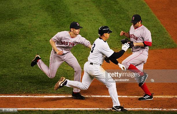 Pitcher Bronson Arroyo of the Boston Red Sox has the ball knocked out of his glove by batter Alex Rodriguez of the New York Yankees on a tagout at...