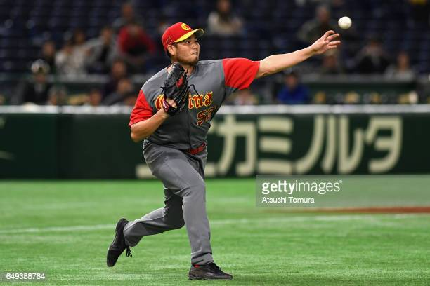 Pitcher Bruce Chen of China throws to the first base after fielding a grounder by Infielder Alexander Ayala of Cuba in the bottom of the third inning...