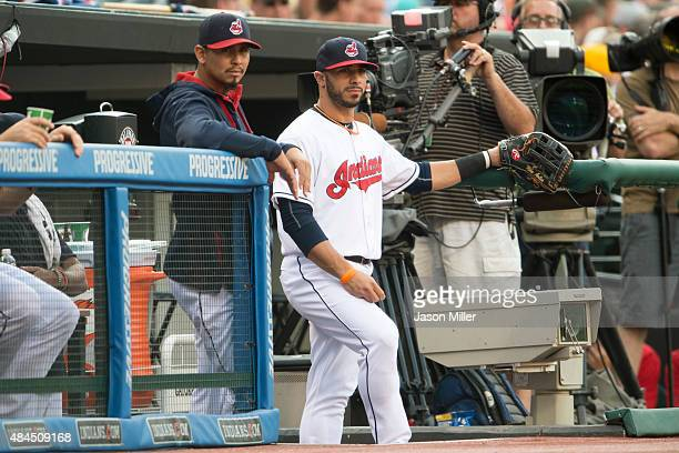 Pitcher Carlos Carrasco and shortstop Mike Aviles of the Cleveland Indians in the dugout prior to the game against the Chicago White Sox at...