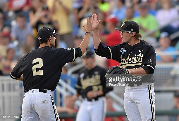 Pitcher Carson Fulmer of the Vanderbilt Commodores reacts to getting the final out against the Virginia Cavaliers in the first inning with teammate...