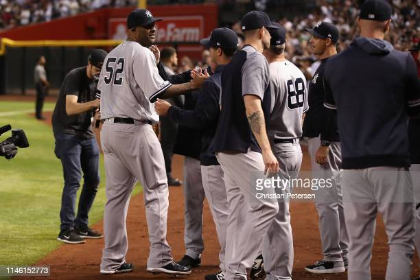 Pitcher CC Sabathia of the New York Yankees is congratulated by teammates after recording his 3000th career strike out against John Ryan Murphy of...