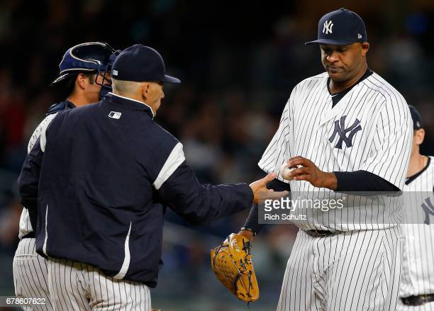 Pitcher CC Sabathia of the New York Yankees is removed by manager Joe Girardi as catcher Kyle Higashioka looks on during the fifth inning of a game...