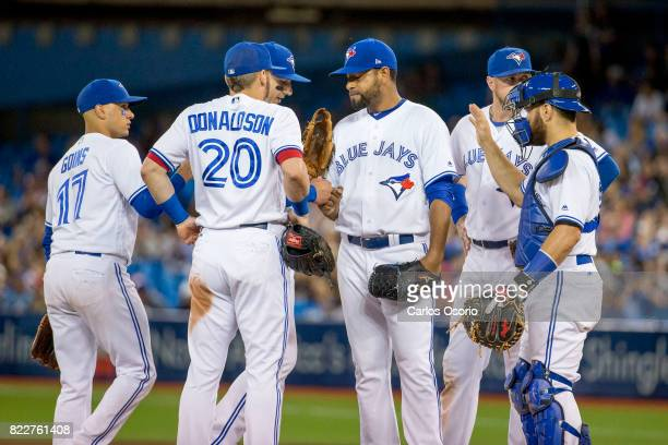 TORONTO ON JULY 25 Pitcher Cesar Valdez of the Blue Jays gets congratulations from his team before being taken out in the 7th inning of MLB action as...