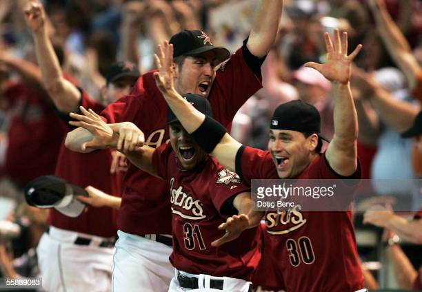 Pitcher Chad Qualls Charles Gipson and Luke Scott of the Houston Astros come out of the dugout to celebrate after Chris Burke hit a solo home run to...