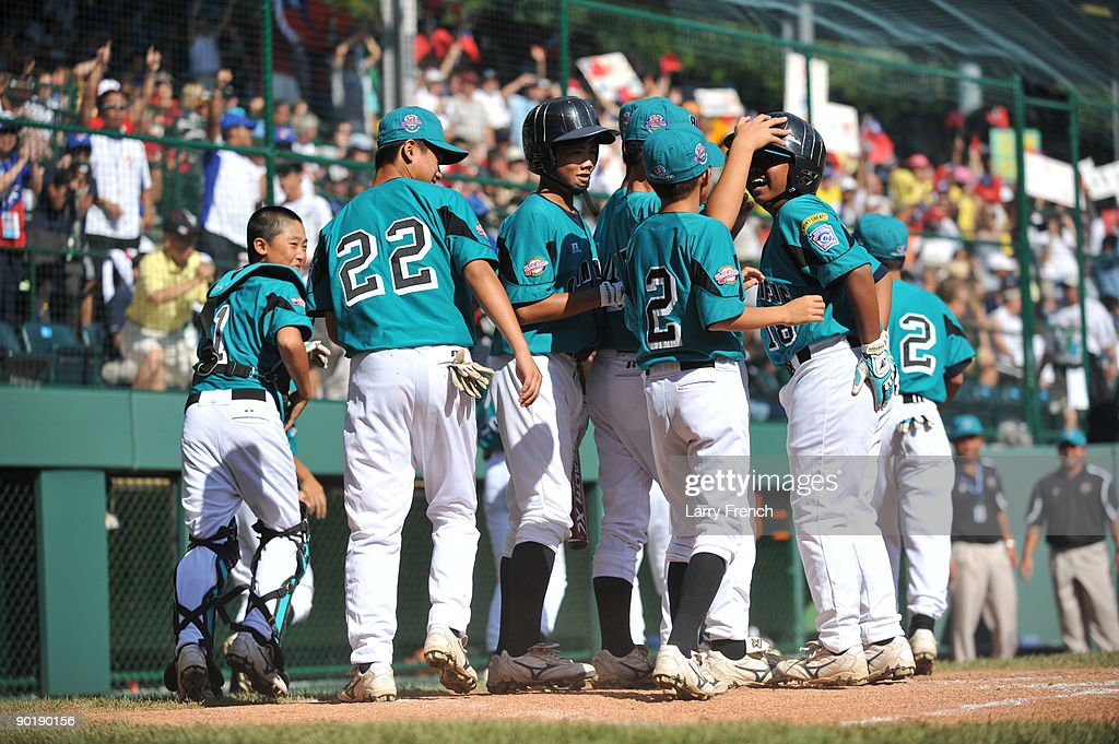 Pitcher Chin Ou #18 of Asia Pacific (Taoyuan, Taiwan) is hugged by teammates after scoring a a run against California (Chula Vista) in the little league world series final at Lamade Stadium on August 30, 2009 in Williamsport, Pennsylvania.