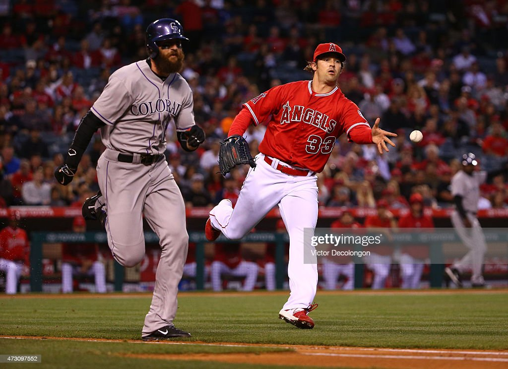 Pitcher C.J. Wilson #33 of the Los Angeles Angels of Anaheim tosses the ball for the force out at first base on a sacrifice bunt by Charlie Blackmon #19 of the Colorado Rockies in the third inning during the MLB game at Angel Stadium of Anaheim on May 12, 2015 in Anaheim, California.