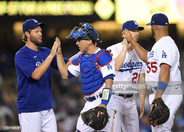 Pitcher Clayton Kershaw of the Los Angeles Dodgers and Walker Buehler congratulate catcher Austin Barnes and Albert Pujols after defeating the...