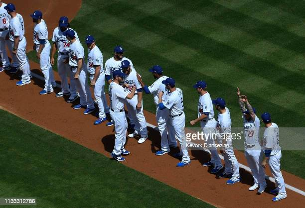 Pitcher Clayton Kershaw of the Los Angeles Dodgers is greeted by his teammates as they line up for an Opening Day game against Arizona Diamondbacks...