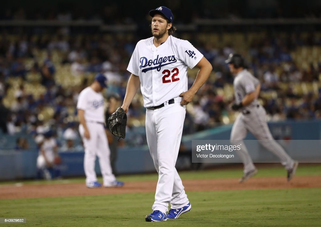 Pitcher Clayton Kershaw #22 of the Los Angeles Dodgers looks on after giving up a three-run homerun in the first inning as DJ LeMahieu #9 of the Colorado Rockies approaches third base in the background during the MLB game at Dodger Stadium on September 7, 2017 in Los Angeles, California.