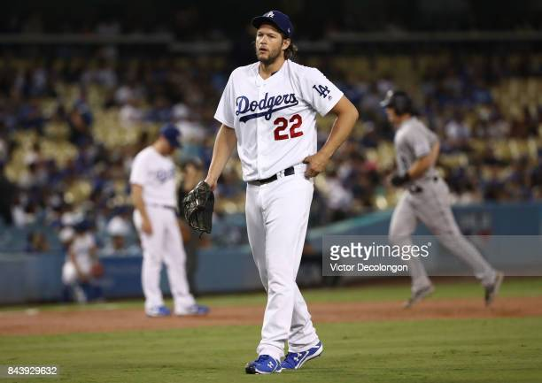 Pitcher Clayton Kershaw of the Los Angeles Dodgers looks on after giving up a threerun homerun in the first inning as DJ LeMahieu of the Colorado...