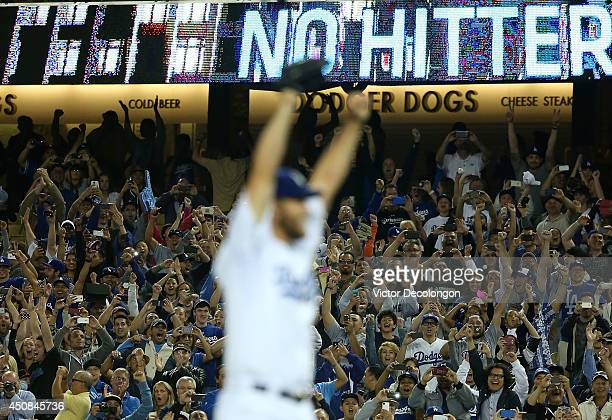 Pitcher Clayton Kershaw of the Los Angeles Dodgers reacts after pitching a no-hitter against the Colorado Rockies as fans jubilate in the background...