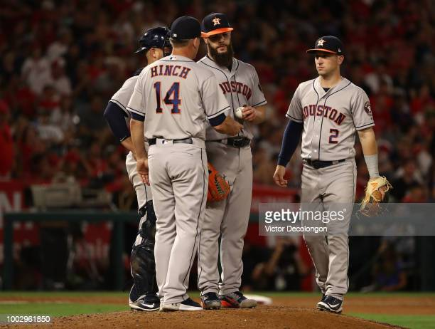 Pitcher Dallas Keuchel of the Houston Astros hands the ball to manager AJ Hinch and leaves the game as teammate Alex Bregman looks on in the eighth...