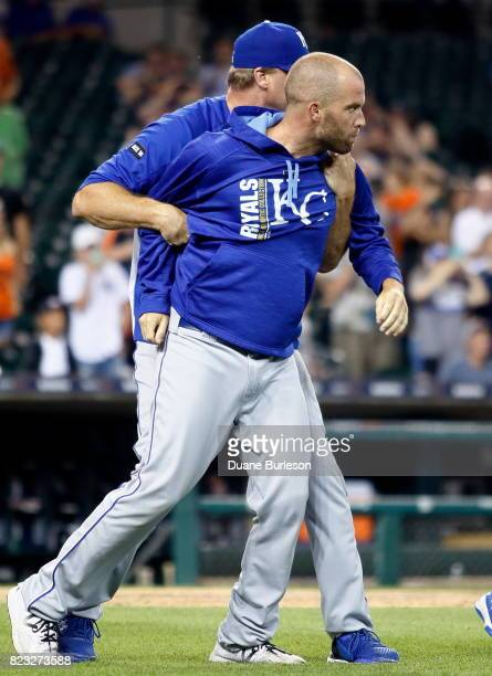 Pitcher Danny Duffy of the Kansas City Royals is held back by assistant hitting coach Brian Buchanan after teammate Mike Moustakas was hit by a pitch...