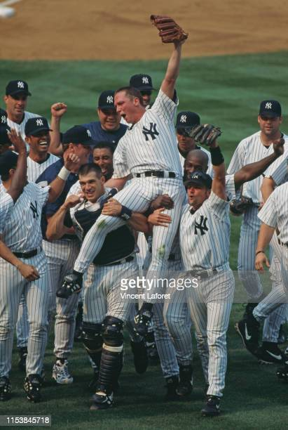 Pitcher David Cone of the New York Yankees celebrates with his team mates after pitching the perfect game during the Major League Baseball American...