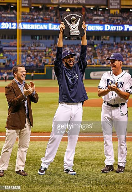Pitcher David Price of the Tampa Bay Rays celebrates his Cy Young award as General Manager Andrew Friedman and pitching coach Jim Hickey look on just...