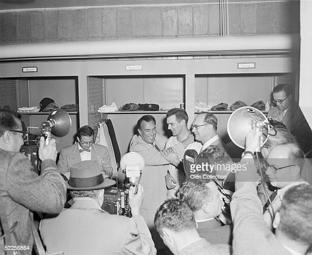 Pitcher Don Larsen of the New York Yankees is congratulated by Yankees' owners Dan Topping and Del Webb in the clubhouse at Yankee Stadium after...