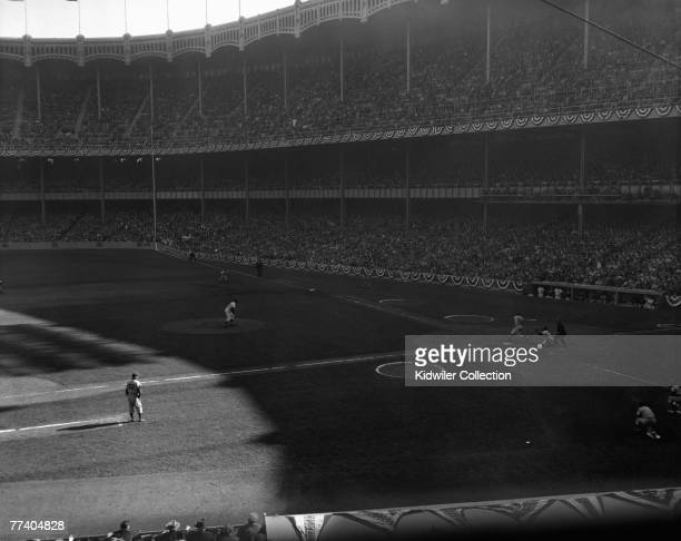 Pitcher Don Larsen of the New York Yankees throws a strike past pinch hitter Dale Mitchell of the Brooklyn Dodgers with two outs in the ninth inning...