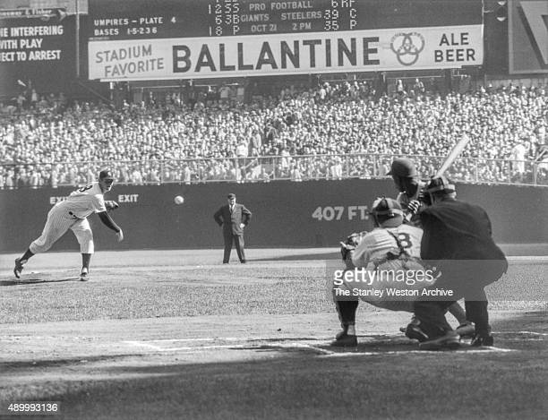 Pitcher Don Larson of the New York Yankees delivers the first pitch to Jim Gilliam of the Brooklyn Dodgers as catcher Yogi Berra and umpire Babe...