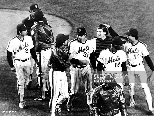 Pitcher Ed Lynch of the New York Mets is congratulated by teammates Ron Darling and catcher Gary Carter as Kelvin Champman and Darryl Strawberry walk...