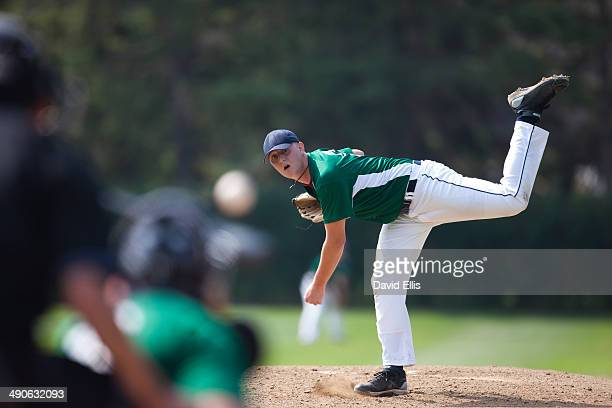 pitcher finishes his windup and delivers a pitch to homeplate. - pitcher stockfoto's en -beelden