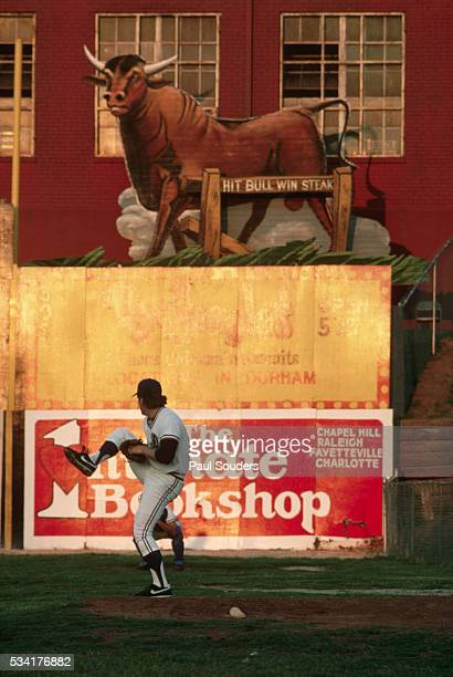 A pitcher for the Durham Bulls warms up in the bullpen next to a sign shaped like a bull A caption on the animal exhorts hitters to homer reading Hit...