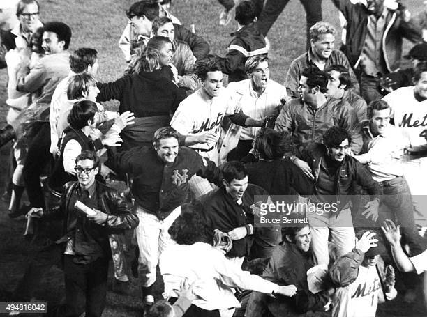 Pitcher Gary Gentry of the New York Mets runs on the field with teammates and fans after defeating the St Louis Cardinals to win the National League...